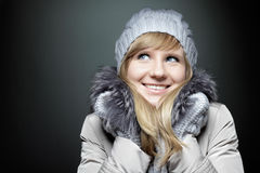 Young beautiful Caucasian woman with blue eyes in winter coat and hat dreamily looking away. Stock Image