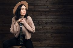 Young beautiful caucasian woman in casual playing small guitar royalty free stock photography