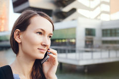 Young beautiful Caucasian woman in casual style clothes is talking on her cellphone standing near modern buildings, smiling. Stock Image