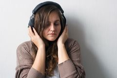 Caucasian woman with curly hair in sweater with headphones royalty free stock image