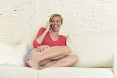 Young beautiful Caucasian woman happy on couch talking on mobile phone relaxed cheerful laughing Royalty Free Stock Photo