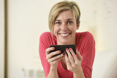Young beautiful Caucasian woman happy using internet app on mobile phone smiling happy Stock Photo