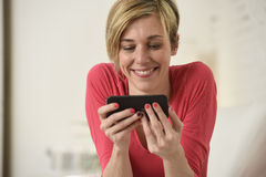 Young beautiful Caucasian woman happy using internet app on mobile phone smiling happy Royalty Free Stock Photography
