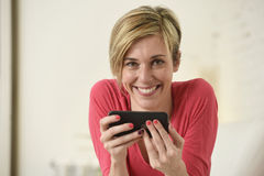 Young beautiful Caucasian woman happy using internet app on mobile phone smiling happy Royalty Free Stock Image