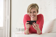 Young beautiful Caucasian woman happy using internet app on mobile phone smiling happy Royalty Free Stock Photo
