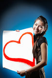 Young beautiful Caucasian woman is holding a big white poster with red painted heart. smiling and looking at camera. Royalty Free Stock Image