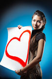 Young beautiful Caucasian woman is holding a big white poster with red painted heart. smiling and looking at camera. Young beautiful Caucasian woman is holding Stock Images