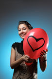 Young beautiful Caucasian woman is holding red balloon with painted heart. Smiling and looking at camera. Stock Photography