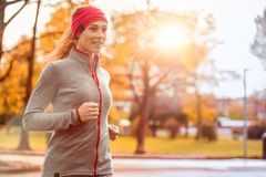 Young beautiful caucasian woman jogging workout training. Autumn running fitness girl in city urban park environment. With fall trees orange. Sunset or sunrise stock images
