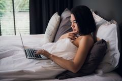 Young beautiful caucasian woman laying on bed and using laptop to work after wake up and thinking about work. Copy space royalty free stock photography