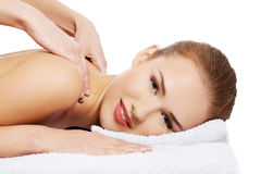 Young beautiful caucasian woman lying on a massage table and is Stock Images