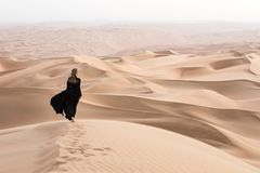 Young woman in Abaya posing in desert landscape. Young beautiful Caucasian woman posing in a traditional Emirati dress - abaya in Empty Quarter desert landscape Stock Images