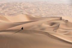 Young woman in Abaya posing in desert landscape. Young beautiful Caucasian woman posing in a traditional Emirati dress - abaya in Empty Quarter desert landscape stock photo