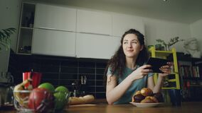 Young beautiful caucasian woman sitting at table in kitchen using digital tablet, she is taking a glance into window. Young beautiful caucasian woman sitting at stock footage