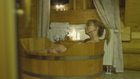 Young beautiful caucasian woman taking bath in a wooden tub. Pretty blond hair woman relaxing in beauty SPA Stock Image