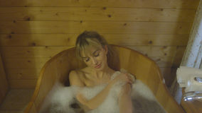 Young beautiful caucasian woman taking bath in a wooden tub. Pretty blond hair woman relaxing in beauty SPA Stock Photo