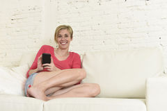 Young beautiful Caucasian woman texting happy using internet on mobile phone in home couch Royalty Free Stock Image
