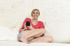 Young beautiful Caucasian woman texting happy using internet on mobile phone in home couch Stock Photos