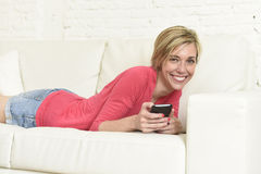 Young beautiful Caucasian woman texting happy using internet on mobile phone in home couch Stock Image