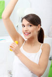 Young beautiful caucasian woman using deodorant Royalty Free Stock Photo