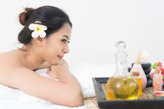 Young beautiful caucasion woman lying on white bed in spa salon Stock Images
