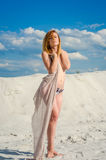 Young beautiful charming girl with long hair in the heat of summer and the weather is sunny walks on the sandy beach in a swimsuit Royalty Free Stock Image