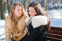 2 young beautiful charming women sitting on a bench in winter park outdoors Royalty Free Stock Photos