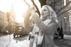 Young beautiful cheerful blond woman taking photos with her vintage film camera on a sunny day at Rynok square in Lviv royalty free stock image