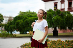 Young beautiful cheerful female student smiling, holding folders outdoors, park background. Royalty Free Stock Photography