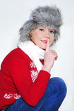 The young beautiful cheerful girl in a fur cap. To a cap with ear-flaps Stock Images