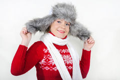 The young beautiful cheerful girl in a fur cap. To a cap with ear-flaps Stock Photos