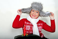 The young beautiful cheerful girl in a fur cap. To a cap with ear-flaps Stock Image