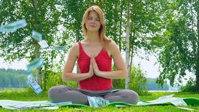 Young beautiful and cheerful girl is meditating in nature on a grassy lawn. Money 100 dollar bill is flying from the. Sky. The concept of a successful and calm stock video footage