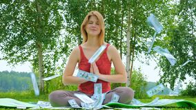 Young beautiful and cheerful girl is meditating in nature on a grassy lawn. Money 100 dollar bill is flying from the. Sky. The concept of a successful and calm stock video