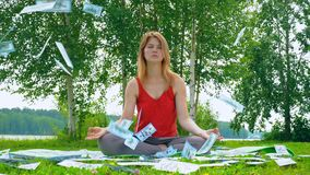 Young beautiful and cheerful girl is meditating in nature on a grassy lawn. Money 100 dollar bill is flying from the stock video footage