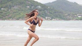 Young beautiful cheerful woman in the bikini is running in freedom fun. stock footage
