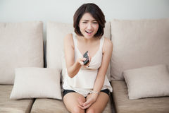 Young beautiful cheerful woman holding remote Stock Image