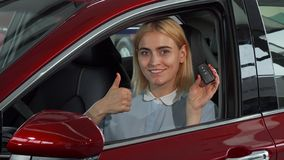 Happy female driver showing her car keys and thumbs up stock image