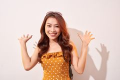 Young beautiful cheerful woman wearing in orange polka dots dress dancing. And posing over beige wall. Good mood. Hands up! People Emotions Beauty Fashion royalty free stock photos