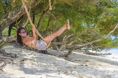 Young beautiful Chinese Asian girl having fun on beach tree swing enjoying happy feeling free in Summer holiday tropical trip. And travel concept Royalty Free Stock Image