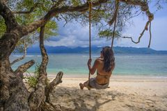 Young beautiful Chinese Asian girl having fun on beach tree swing enjoying happy feeling free in Summer holiday tropical trip Stock Photography