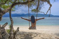 Young beautiful Chinese Asian girl having fun on beach tree swing enjoying happy feeling free in Summer holiday tropical trip Royalty Free Stock Photos