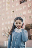 Young beautiful Chinese girl with headphones Royalty Free Stock Image