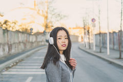 Young beautiful Chinese girl with headphones Stock Photo