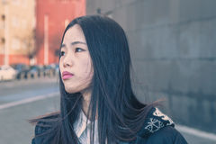 Young beautiful Chinese girl posing in the city streets Royalty Free Stock Photography