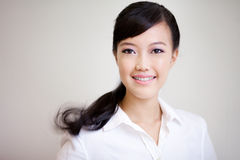 Young, beautiful chinese woman smiling. Shot with soft lighting together with vignetting and some motion blur at the pony tail to give a strong feeling of Royalty Free Stock Images