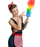 Young beautiful cleaning woman holding static duster and pointing to the right Royalty Free Stock Photos
