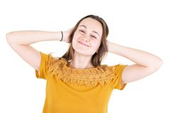 Young beautiful close eyes woman in yellow undershirt poses and smiles isolated on white background. A Young beautiful close eyes woman in yellow undershirt royalty free stock photos