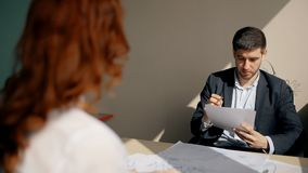 Young beautiful colleagues working with contract sitting at table in modern office. Young beautiful colleagues working with contract sitting at table in modern stock footage