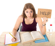 Young beautiful college student girl studying for university exam in stress asking for help under test pressure. Young beautiful college student girl studying Stock Photo